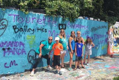 Photo: The artists taking a picture in front of the freshly painted wall