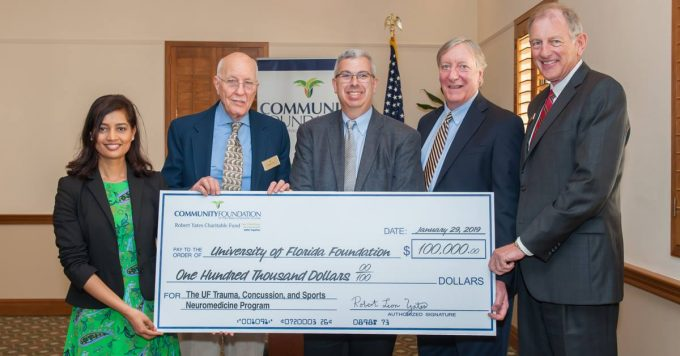 Photo of Donation check and From left: Robert and Ellen Yates Fellow Dr. Shae Datta, Mr. Yates, TRACS director Dr. Michael Jaffee, Dr. Russell Bauer and Bradley Hurlburt, president and CEO of Community Foundation for Palm Beach and Martin Counties.
